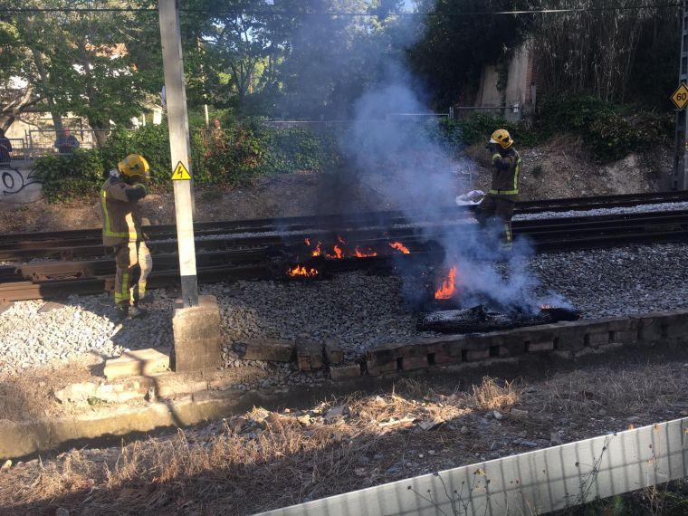 Els bombers aparten el tronc i els neumàtics incendiats per restablir la circulació de trens